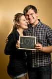 Couple in love holding blackboard with written word Stock Photos