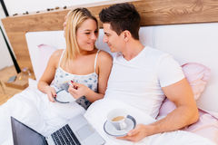 Couple in love holding coffee while in bed. Couple in love holding cups of coffee and smiling Stock Photo