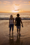 Couple in love and holding hands at the beach at sunset Royalty Free Stock Photography