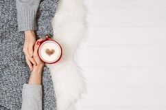 Couple holding hands with coffee on white table, top view. Couple in love holding hands with coffee on white wooden table. Photograph taken from above, top view Royalty Free Stock Image