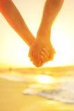 Couple in love holding hands - happy relationship. Closeup of male and female arms together at beach sunset during holidays tropical vacations Royalty Free Stock Image