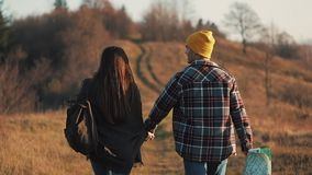 Couple in love holding hands hiking outdoors. Hikers man and woman trekking walking with backpacks in trail at sunset in. Mountains stock footage