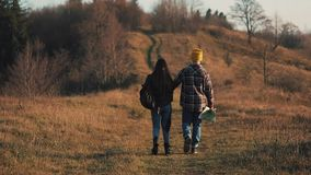 Couple in love holding hands hiking outdoors. Hikers man and woman trekking walking with backpacks in trail at sunset in. Mountains stock video