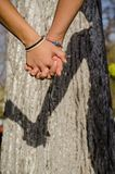 Couple in love holding hands hot summer day outside in the nature. Young girl and boy with hands together expressing beautifu. Couple in love holding hands in a Royalty Free Stock Photography