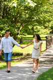 Couple in love holding hands walking park Stock Photos