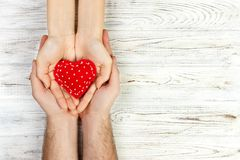 Couple in love holding a red heart in their hands. Valentine day concept. copy space.  Stock Photos