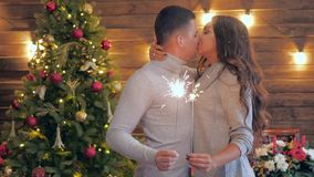 Couple in love holds bengal lights and kisses on the background of Christmas tree
