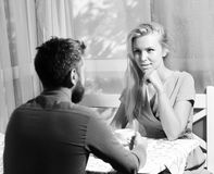 Woman and flirty face and man have an affair. Couple in love holds cups of coffee at table. Woman and flirty face and men have an affair. Girl with blond hair royalty free stock photo
