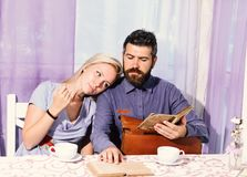 Couple in love holds cups of coffee at table. Woman and man with dreamy faces have an affair. Couple in love holds cups of coffee at table. Woman and men with stock image
