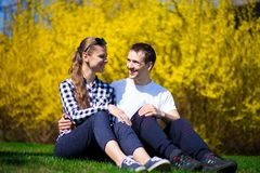 Couple in love hug in park on fresh green grass near tree in yellow blossom. Spring time Stock Photo