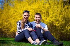 Couple in love hug in park on fresh green grass. Near tree in yellow blossom. Spring time Royalty Free Stock Photography