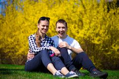 Couple in love hug in park on fresh green grass near tree in yellow blossom. Spring time Stock Photography