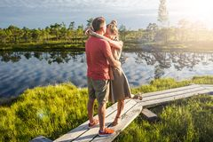couple in love hugging each other on wooden bridge with green trees and river royalty free stock photography