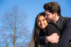 Couple in love hugging and kissing outside Stock Images