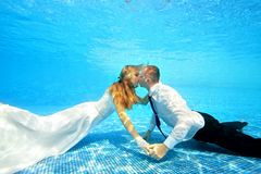Couple in love hugging and kissing underwater at the bottom of the pool. Horizontal orientation. A view from under the water from the bottom of the pool Stock Photo
