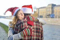 Couple in love hugging  outdoors wearing Christmas hats Royalty Free Stock Photos