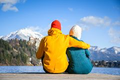 Couple in love hugging together with colorful cloths sitting and relaxing on a wooden pier on a clear sky sunny winter day view fr. Om the back, Bled stock photography