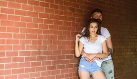 Couple in love hugs brick wall background. Couple find place to be alone. He will never let her go. Girl and hipster. Romantic date intimacy moment. Couple royalty free stock images