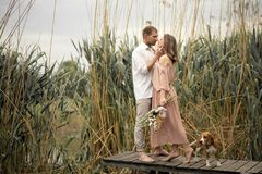 Couple in love hugs and kissing at wooden pier in village. Couple in love hugs and kissing at wooden pier at nature Stock Image