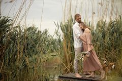 Couple in love hugs and kissing at wooden pier in village. Couple in love hugs and kissing at wooden pier at nature Stock Images