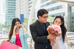 Couple in love and jealous friend. Businessman give flower bouquet to cute girlfriend while beautiful girl behind get jealous. Couple in love and a jealous Stock Photography