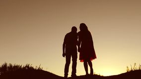 Couple in love kiss walking on silhouette nature sunset slow motion video. Man and woman silhouette of a love walk with stock video