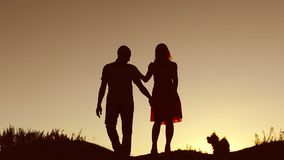 Couple in love kiss walking sunset on silhouette nature slow motion video. Man and woman silhouette of love walk with a. Couple in love kiss walking sunset stock video