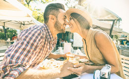 Couple in love kissing at bar eating street food by travel. Couple in love kissing at bar eating local delicacie on travel excursion - Young happy tourists royalty free stock photos