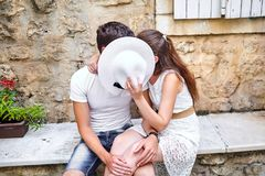 Couple in love kissing behind white female hat on the stone bench in old city. Young man and woman hugging. Summer sunny day royalty free stock image
