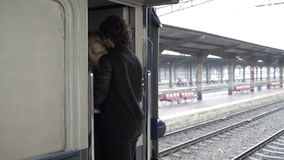 Couple in love kissing and hugging goodbye in railway station before departing on rainy day stock footage