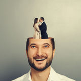 Couple in love kissing in the man's head. Happy young businessman with open head. couple in love kissing and standing in the man's head. photo over grey Stock Image