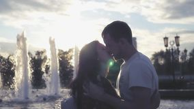 Couple in love kissing near fountain on sunset background. HD, 1920x1080. Slow motion stock video footage