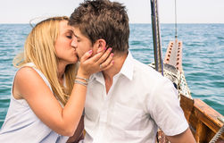 Couple in Love kissing on a sailing Boat in the middle of the Sea. Romantic portrait of a couple in love kissing on a sailing boat in the middle of the Sea in a Stock Photo