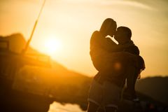 Couple in love kissing at sunset. Silhouette stock image