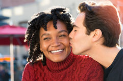 Couple in love kissing. Young african women is smiling while her boyfriend kissing her on the cheek. Close up face of young men kissing in woman's cheek while Stock Photos