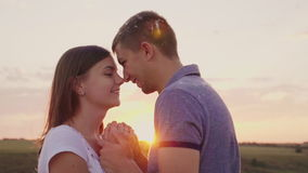 A couple in love lies facing each other at sunset. Around fly feathers after the fight with pillows stock footage