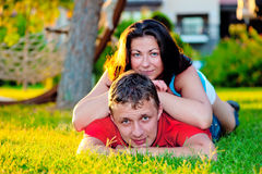 Couple in love lies on a green lawn Stock Photos