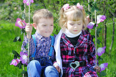 Couple in love little kids on the swings Royalty Free Stock Photos