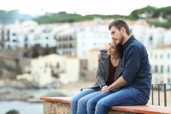 Couple in love looking away on a ledge on vacation royalty free stock photography