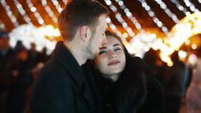 Couple in love looking at the New Year tree of the city, hugs and kiss, bokeh of lights from the Christmas garland nd