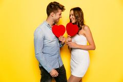 Couple in love looking to each other holding red hearts. Handsome men and beautiful women have fun together, holding red hearts while celebrating Valentine`s day Stock Photos