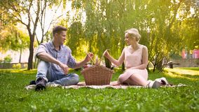 Couple in love looking what they have for picnic in basket, wonderful rest Royalty Free Stock Photos
