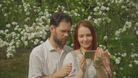 A couple in love looks at photos on the smartphone screen and takes a selfie. stock footage