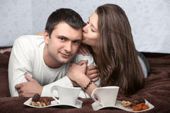 Couple in love. Couple lying on the bed and the girl kisses the guy Stock Photos