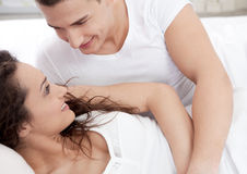 Couple in love lying in bed Stock Images