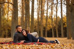Couple in love lying on a blanket. In autumn park Stock Photo