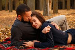 Couple in love lying on a blanket. In autumn park Stock Photography
