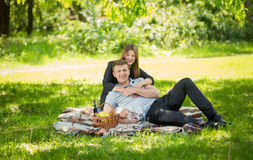 Couple in love lying on blanket under big tree at park Royalty Free Stock Photo