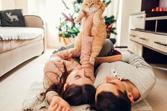 Couple in love lying by Christmas tree and playing with cat at home. Man and woman lifting pet in hands. Couple in love lying by Christmas tree and playing with stock photos