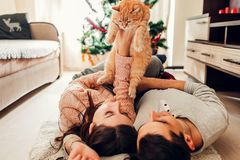 Couple in love lying by Christmas tree and playing with cat at home. Man and woman lifting pet in hands. Couple in love lying by Christmas tree and playing with royalty free stock image